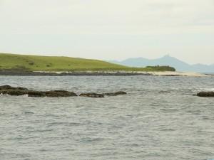 Hòn Dứa ngoài khơi huyện Tuy An, Phú Yên. Bãi đá đen phía trước Hòn Dứa là một phần của bãi đá cạn được gọi là Hòn Than. Xa xa phía nam đằng sau Hòn Dứa là núi Đá Bia.