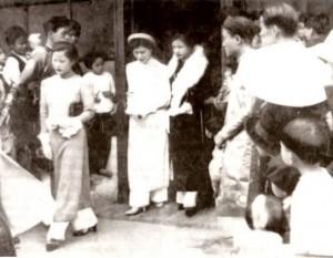 Đám cưới họa sĩ Cát Tường, Bắc Ninh 1936. Chú rể đứng phía trái, đang giang hai tay. Cô dâu Nguyễn Thị Nội mặc áo trắng, đi bên cạnh phù dâu, đều mặc áo Le Mur.